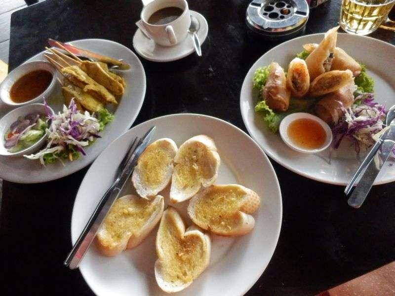 Knoblauchbrot, Frühlingsrollen und Hähnchenspieße mit Erdnussoße